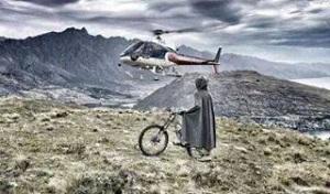Helicóptero tenta investigar o que faz o barman no topo desta montanha e o feliz ciclista observa que chegou na mesma altura do aparelho!