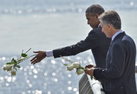 "US President Barack Obama (L) and Argentinian President Mauricio Macri throw a bouquet of white flowers into the River Plate as they pay homage to Dirty War's victims at the ""Parque de la Memoria"" (Remembrance Park) in Buenos Aires on March 24, on the 40th anniversary of the 1976 military coup. Obama paid tribute Thursday to victims of Argentina's former Washington-backed dictatorship at a memorial on the banks of the River Plate, a monument to the estimated 30,000 people who were killed or went missing under the 1976-1983 military regime. AFP PHOTO / NICHOLAS KAMM / AFP / NICHOLAS KAMM"